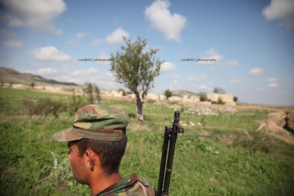 A young armenian recruit carry a Kalashnikov near the frontline to Aserbaijan in the Agdam region in Nagrono Karabakh.