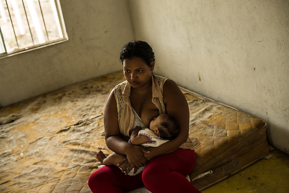 TENOSIQUE, MEXICO - JULY 2, 2014: Ruth Maribel Flores, 28, breastfeeds her 2-month old daughter, Genesis Gonzalez on a worn mattress at the 72 Migrant Shelter. Flores said her family was given an hour to surrender their home in Tegucigalpa under threat of death by gang members, who suspected her 9-year-old son was a lookout for a rival faction. He, too, is traveling with her along with her husband, Carlos Gonzalez, and they plan to work with shelter workers to seek a Mexican visa to allow them to say at least temporarily. She had to leave two of her other children in Honduras with family members, and said through tears that it was the hardes thing that she had ever had to do in her life. PHOTO: Meridith Kohut for The New York Times