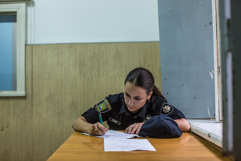 LVIV, UKRAINE - SEPTEMBER 16, 2015: Tetiana Soroka, 25, a member of the new Lviv police, fills out paperwork connected with the arrest of Vladimir, 26, after he was found intoxicated and sleeping in the city's central square and then swore at police officers in Lviv, Ukraine. In an effort to reform the notoriously corrupt Ukrainian police force, an entirely new force has been established in several cities, including Kiev and Lviv, with a primary focus on patrolling the streets. CREDIT: Brendan Hoffman for The New York Times