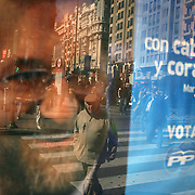 Pedestrians walk past an election poster for Spain's Popular Party leader, Mariano Rajoy, in Madrid, Spain, on Wednesday, March 5, 2008. The March 9 election will be a rematch of the 2004 contest in which Zapatero scored a shock victory over Rajoy three days after Islamist bombings of Madrid commuter trains. Photographer: