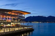 The Vancouver Convention Center in the early evening. Photographed from the area in between the Vancouver Convention Center and Canada Place in Vancouver, British Columbia, Canada.  The North Shore Mountains (and North Vancouver) are in the background accross Burrard Inlet.