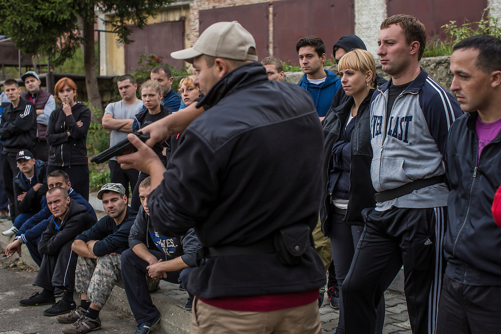 LVIV, UKRAINE - OCTOBER 5, 2015: Instructor Yurii Shevchyk, center, teaches recruits how to apprehend a suspect during a traffic stop during tactical training for new patrol police officers in Lviv, Ukraine. In an effort to reform the notoriously corrupt Ukrainian police force, an entirely new force has been established in several cities, including Kiev and Lviv, with a primary focus on patrolling the streets. CREDIT: Brendan Hoffman for The New York Times