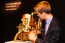 """London, November 7th 2014. Sotheby's is to hold its Inaugural 20TH Century Art– A Different Perspective sale on November 12th in London, where collectors will have the opportunity to acquire some highly regarded examples of avante-garde and abstract art. PICTURED: Sotheby's Richard Lowkes examines Georg Hartmann's """"Mechanical Head"""", which is expected to fetch between £15,000 to £20,000 at auction."""