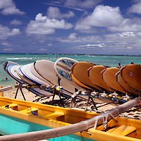 Surfboards and outrigger canoes await rental on Waikiki Beach in Honolulu, Oahu, Hawaii.