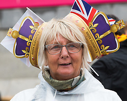 Trafalgar Square, London, June 12th 2016. Rain greets Londoners and visitors to the capital's Trafalgar Square as the Mayor hosts a Patron's Lunch in celebration of The Queen's 90th birthday. PICTURED: A woman wears two crowns as she gets into the spirit of the occasion.