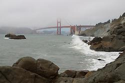 Waves break on the rocks near the foot of the Golden Gate Bridge in San Francisco, California.