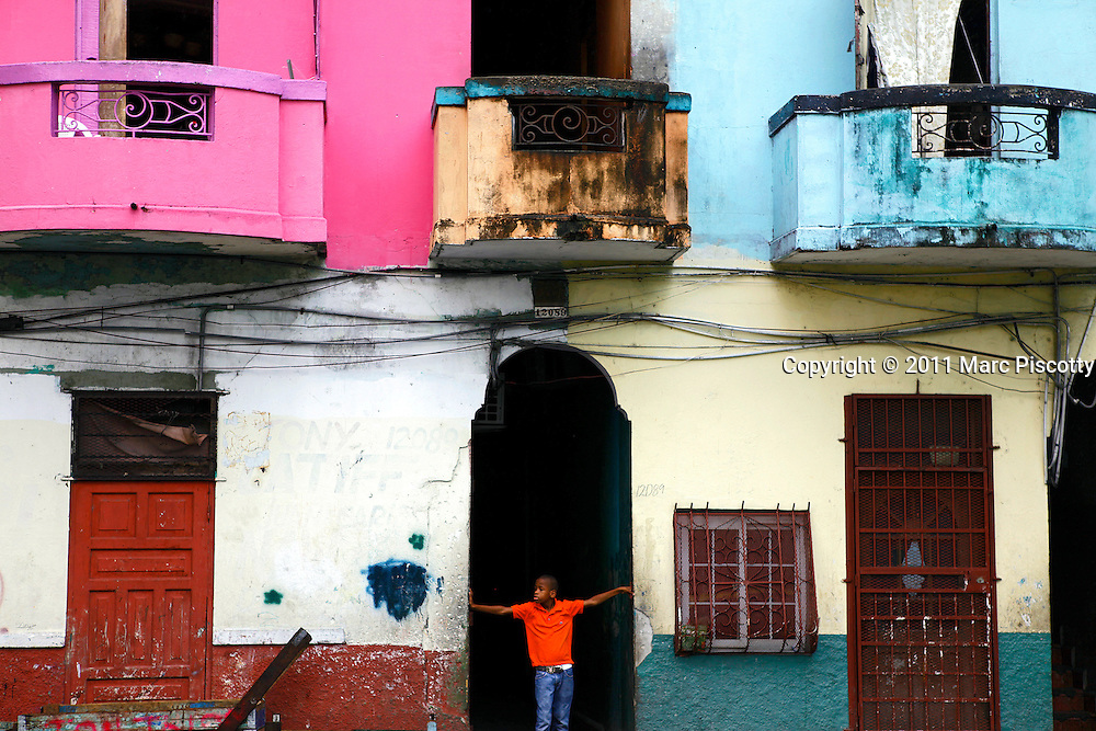 SHOT 3/19/11 2:33:04 PM - A young boy stands in a doorway in Colon, Panama. Colón is a sea port on the Caribbean Sea coast of Panama. The city lies near the Atlantic entrance to the Panama Canal. It is capital of Panama's Colón Province and has traditionally been known as Panama's second city. During its heyday, Colón was home to dozens of night clubs, cabarets and movie theaters. It was known for its citizens' civic pride, orderly appearance and outstanding native sons and daughters. Politically-instigated riots in the 1960s destroyed the city's beautiful municipal palace and signaled the start of the city's decline, which was further accelerated by the military dictatorships of Omar Torrijos and Manuel Noriega from 1968-1989..Since the late 1960s, Colón has been in serious economic and social decline. In recent times, the unemployment rate has hovered around 40% and the poverty rate is even greater than that. Drug addiction and poverty have contributed to crime and violence issues which successive Panamanian governments have not addressed effectively. (Photo by Marc Piscotty / © 2011)
