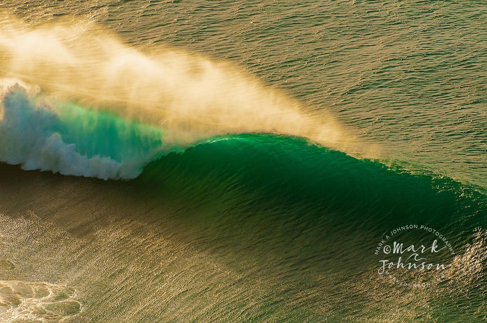 Aerial view of a backlit wave breaking off the Na Pali coast of Kauai, Hawaii