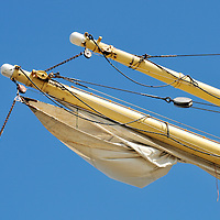 Sailboat yardarm with furled sail, rigging and block and tackle