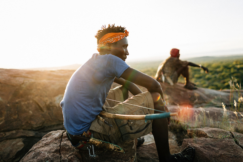 Benja, 20, of the Hazda tribe, sits on a rock at dusk, Yaeda valley, Northern Tanzania. Photo by Greg Funnell, March 2016