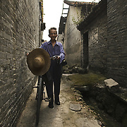Old man with bycicle walks through the ancient Cha Tang Village, at Guangzhou periphery. Guangdong, China.