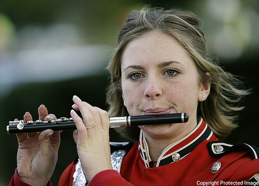 A band member warms up her flute before homecoming.