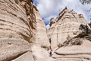 """Slot Canyon Trail. See fantastic hoodoos and a great slot canyon in Kasha-Katuwe Tent Rocks National Monument, in New Mexico, USA. Hike the easy Cave Loop Trail plus Slot Canyon Trail side trip (3 miles round trip), 40 miles southwest of Santa Fe, on the Pajarito Plateau. Distinctive cone-shaped caprocks protect soft pumice and tuff beneath. Geologically, the Tent Rocks are made of Peralta Tuff, formed from volcanic ash, pumice, and pyroclastic debris deposited over 1000 feet thick from the Jemez Volcanic Field, 7 million years ago. Kasha-Katuwe means """"white cliffs"""" in the Pueblo language Keresan. This panorama was stitched from 4 overlapping photos."""