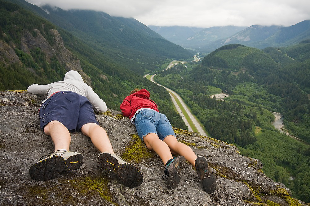 Siblings Elliot and Maddie Swanson look out over Interstate 90 and the South Fork Snoqualmie River from the top of the Exit 38 rock climbing crag outside North Bend, Washington. Exit 38 is a sport climbing area popular for its proximity to Seattle.