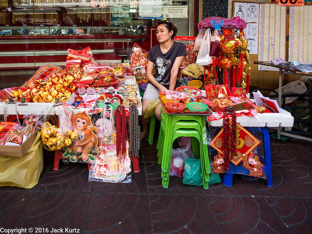 """04 FEBRUARY 2016 - BANGKOK, THAILAND: A vendor selling Chinese New Year decorations waits for customers in Bangkok's Chinatown district, before the celebration of the Lunar New Year. Chinese New Year, also called Lunar New Year or Tet (in Vietnamese communities) starts Monday February 8. The coming year will be the """"Year of the Monkey."""" Thailand has the largest overseas Chinese population in the world; about 14 percent of Thais are of Chinese ancestry and some Chinese holidays, especially Chinese New Year, are widely celebrated in Thailand.      PHOTO BY JACK KURTZ"""