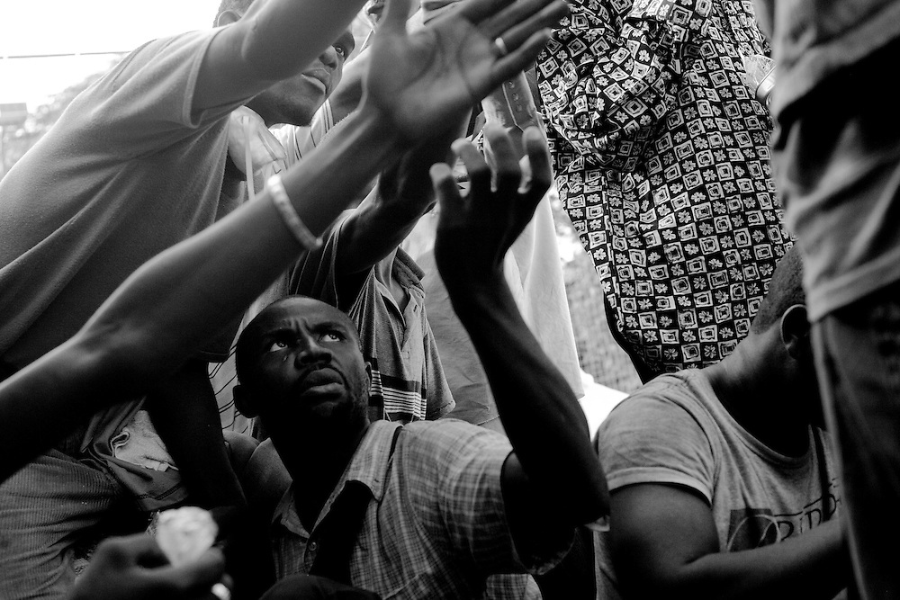 Men reach for a snack after unloading food aid for victims of the recent earthquake in Port-au-Prince, Haiti.