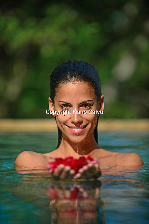 Young attractive woman holding red flowers in an infinity edge swimming pool. The Dutch House, Galle, Sri Lanka