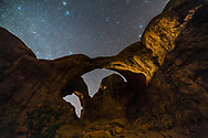A dark, moonless sky behind Double Arch in Arches National Park, Utah, with a wash of car headlights providing some highlights to the rocks. High clouds added the natural star glows. <br />
