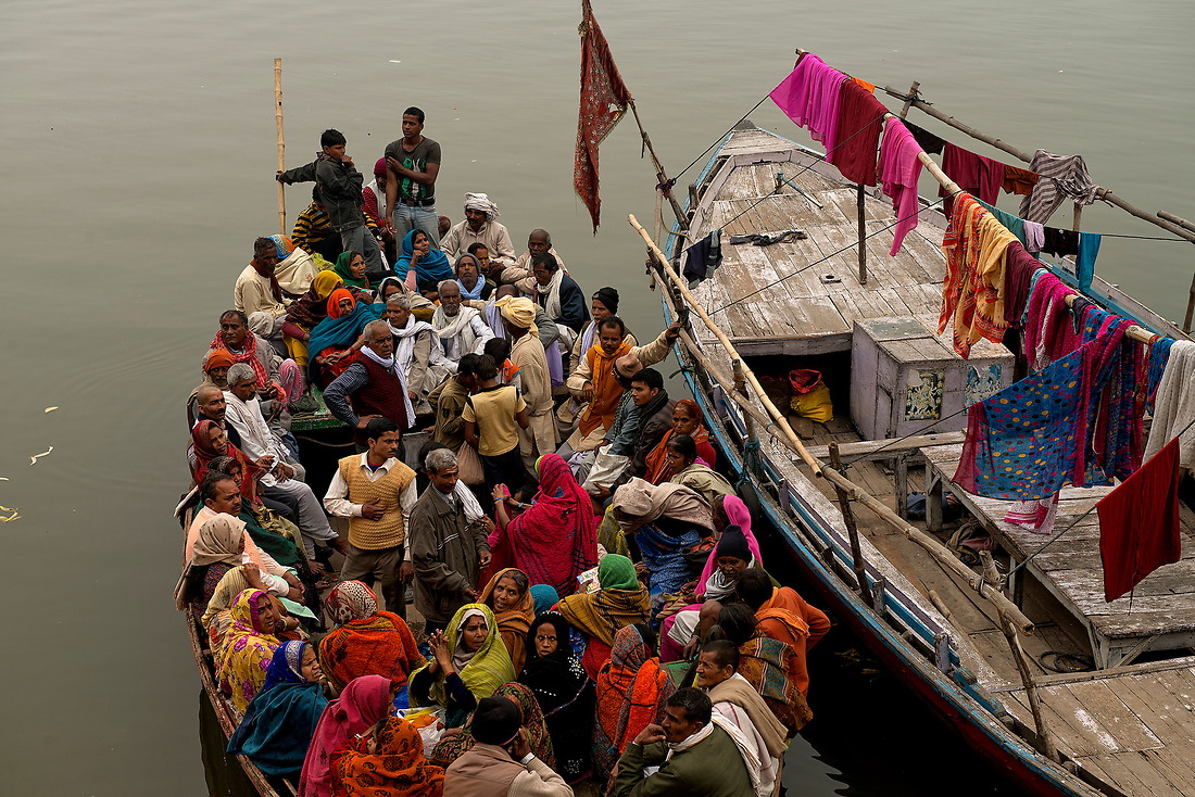 A boat comes ashore on the banks of Varanasi after crossing the river Ganges delivering its passengers to the ghat (a series of steps leading down to a body of holy water) where they will bathe on February 2, 2013 in Varanasi, India. — © Jeremy Lock/