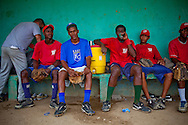 Baseball players for the Warriors sit in the dugout during practice at the municipal stadium on Thursday, February 25, 2010 in San Antonio de Guerra, Dominican Republic.
