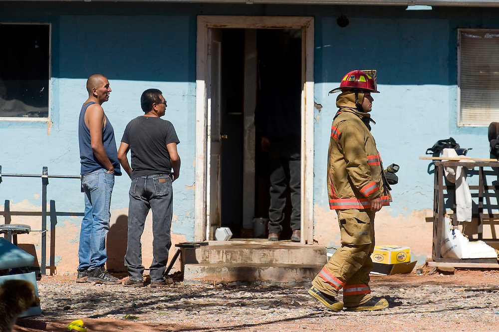 041312       Brian Leddy.A Navajo Pine fireman works at the scene of a fire at a home in Iyanbito Friday morning. The fire was extinguished quickly by officials from various fire departments. .