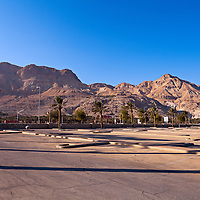 Barren hills along the Dead Sea coast are the backdrop for the Ein Gedi beach parking lot.