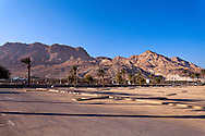 Barren hills along the Dead Sea coast are the backdrop for the Ein Gedi beach parking lot. WATERMARKS WILL NOT APPEAR ON PRINTS OR LICENSED IMAGES.