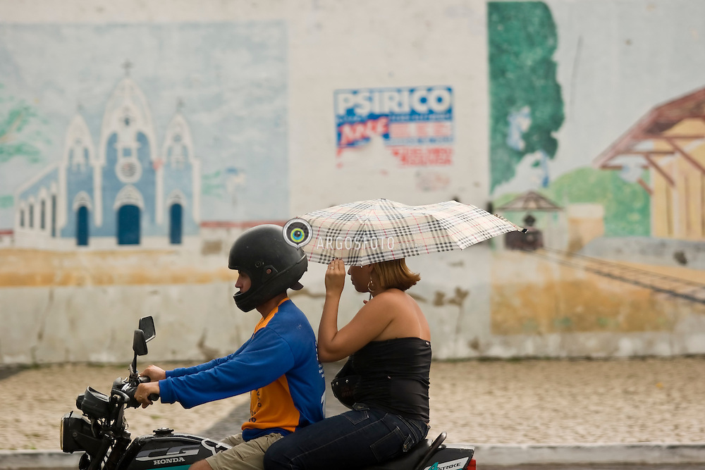 Centro da cidade de Delmiro Gouveia, em Alagoas. Mulher passando em frente a mural representando a Igreja da cidade/ Woman with unbrella crossing in front of a wall painted, representing the city of Delmiro Gouveia.Foto Marcos Issa