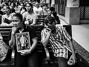 """11 APRIL 2017 - BANGKOK, THAILAND:  A woman holds a photo of Bhumibol Adulyadej, the Late King of Thailand, while she waits for her train in Hua Lamphong train station during the Songkran travel period at Hua Lamphong train station in Bangkok. Songkran is the traditional Thai Lunar New Year. It is celebrated, under different names, in Thailand, Myanmar, Laos, Cambodia and some parts of Vietnam and China. In most places the holiday is marked by water throwing and water fights and it is sometimes called the """"water festival."""" This year's Songkran celebration in Thailand will be more subdued than usual because Thais are still mourning the October 2016 death of their revered Late King, Bhumibol Adulyadej. Songkran is officially a three day holiday, April 13-15, but is frequently celebrated for a full week. Thais start traveling back to their home provinces over the weekend; busses and trains going out of town have been packed.    PHOTO BY JACK KURTZ"""