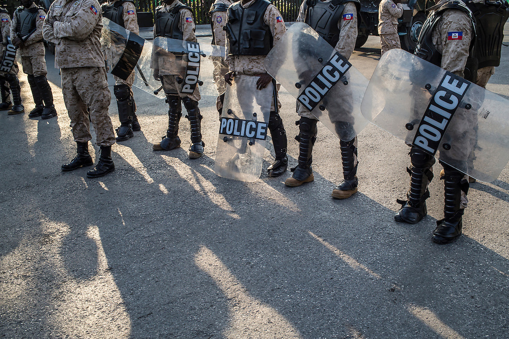 Riot police stand guard against anti-government protesters on Saturday, December 13, 2015 in Port-au-Prince, Haiti. The police have been frequently accused of using excessive force against demonstrators, and on this day one protester, Nicolas Jolin, was alleged to have been shot and killed by police while protesting.