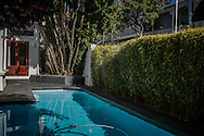 Inside the security bubble.  A quaint guesthouse swimming pool near Dunkley Square surrounded by electrified wire reinforcing a seige mentality in Central Cape Town.  South Africa.