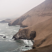 """Pan-American Highway 1 clings to a cliff above the South Pacific Ocean in the coastal desert north of Lima, in Peru, South America. From May to October along the coast of Peru, the heavy fog called """"garua"""" blocks the sun but drops almost no rainfall, just a fine mist, enough to wet desert plants on high coastal hills. In contrast, around this time, the high Andes are generally sunny, warm, and dry (from June to September), great for trekking or touring."""