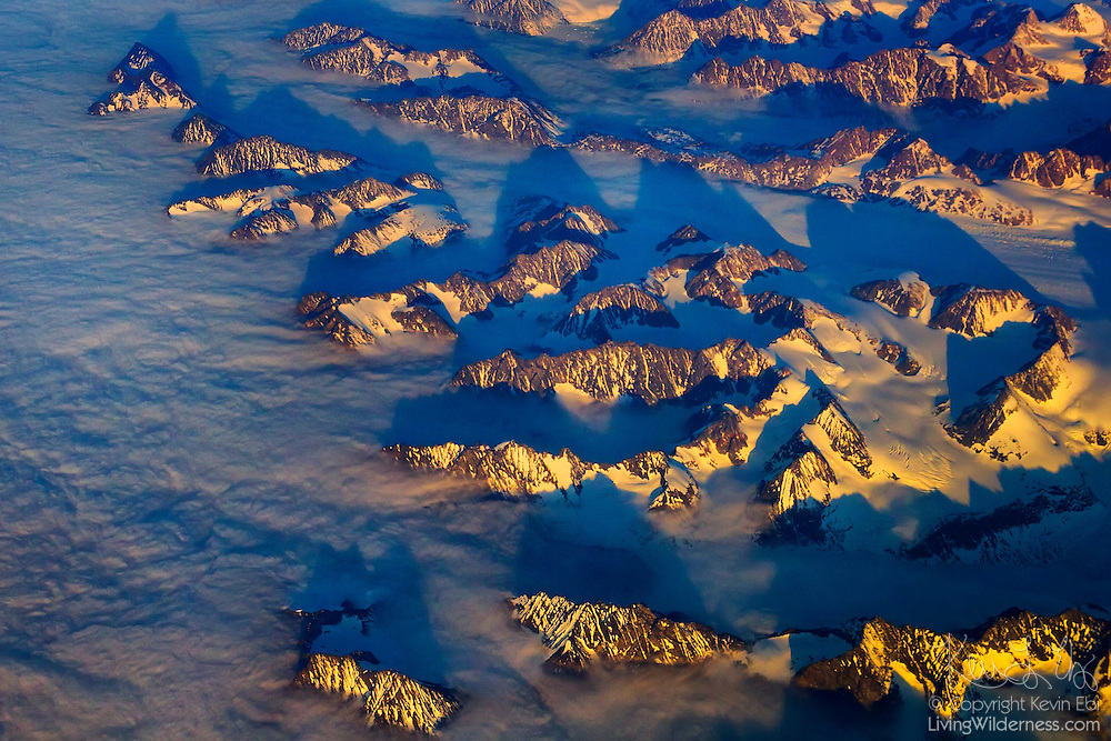 The summits of tall coastal mountains poke out from a layer of low clouds in this aerial view of the eastern Greenland coast near Tasiilaq.