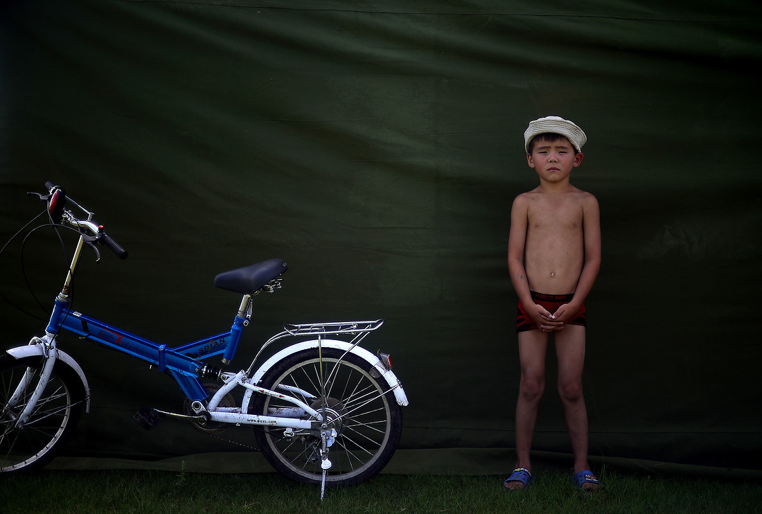 A young herder boy parks his bike by a tent  so he can  watch the Mongolian veterinarian Border Forces inside perform a routine surgery on a sheep. The Border Forces work with the herders teaching and promoting veterinarian and Public Health best practices. — © Jeremy Lock/USAF