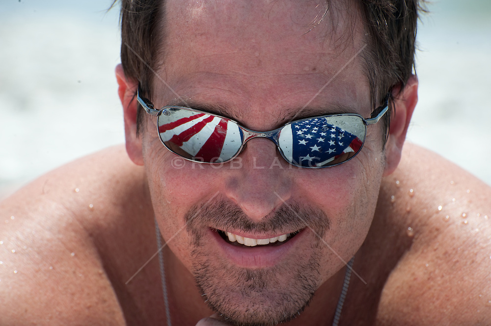 Man on the beach wearing sunglasses reflecting The American Flag