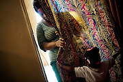 "Gabby, 2, hides behind a curtain in the apartment she shares with her mother, Lettorea ""Lottie"" Clark, 25, in Albany, GA on Wednesday, October 22, 2008. Lottie and Gabby live off welfare after escaping an abusive relationship with Gabby's father."
