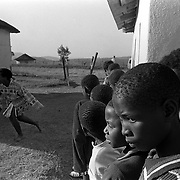 A young girl runs out of a room after having been examined for virginity by a group of mothers in Magqabasini village, near Flagstaff in the former Transkei July 20, 1999, as others wait their turn.  This tradition has been revived to combat child abuse and high rates of teenage pregnancies and the spread of HIV. (Greg Marinovich)