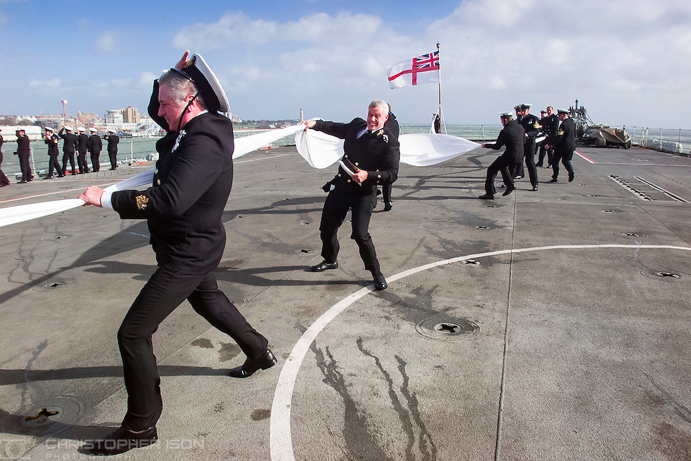 Officers struggle to control the Paying Off Pennant aboard HMS Fearless as they enter Portsmouth Harbour where it will be decommissioned. Fearless is the last steam driven ship in the Royal Navy.