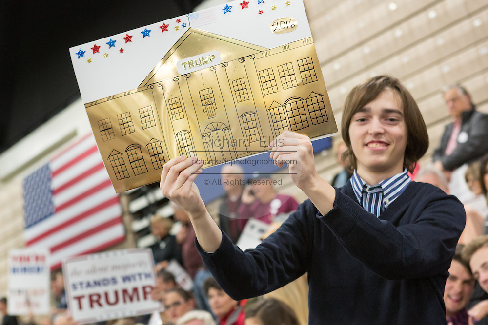 A supporter of Republican presidential candidate billionaire Donald Trump holds a sign showing a gold plated White House before the start of a campaign rally at the Myrtle Beach Convention Center November 24, 2015 in Myrtle Beach, South Carolina.