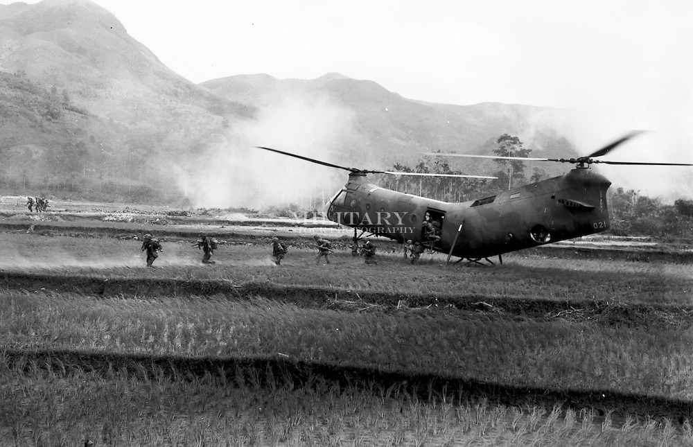 """Under fire in the landing zone, an H-21 Shawnee helicopter delivers Vietnamese Rangers to a """"hot"""" LZ in the central highlands.  Buildings burn in the background after close air support aircraft strikes set them on fire.  Combat operations in Viet Nam, 1962-63, 8th Transportation Company, Qui Nhon RVN.  Photograph by Hans Halberstadt."""