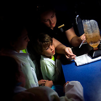 NAPLES, FL -- March 13, 2010 -- Manager Kristina MacNicol shows children including Nate Hedrick, 5, of Summit, New Jersey, center, how to collect brine shrimp in the lab during the Nature's Wonders program at The Ritz-Carlton in Naples, Fla., on Saturday, March 13, 2010.  The three hour programs let kids experience a more involved, educational nature program while parents get free time to enjoy themselves sans kids.