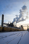 A coal train moves through the cold and snow past the ADM grain mill in Clinton, IA.
