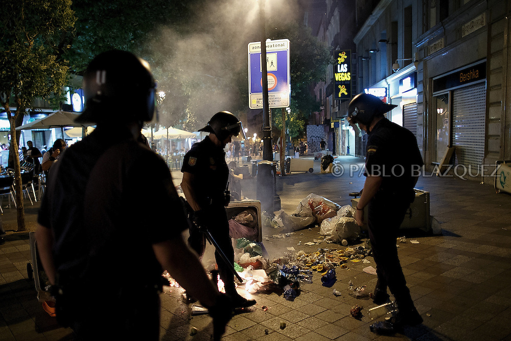 Riot policemen stand next to a barricade during a demonstration against the Spanish government, on Thursday, July 18, 2013, in Madrid, Spain. Thousands demonstrators demanding the resignation of Prime Minister Mariano Rajoy and its party gathered in front of the People's Party headquarter. Rajoy rejected demands to resign after more alleged secret payments and test messages related to former political party treasurer Luis Barcenas under investigation appeared. The spectacle of alleged greed and corruption has enraged Spaniards hurting from austerity and sky high unemployment.
