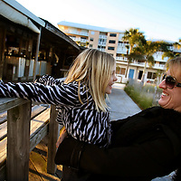 ST. PETE BEACH, FL -- February 13, 2010 -- Eva Myers and her daughter, Avery, 6, both of Tampa, have some fun while taking int he sunset at the Postcard Inn in St. Pete Beach, Fla., on Saturday, February 13, 2010.  The beachfront U-shaped hotel, originally built in 1957, was renovated into a throwback surf shack of sorts with rooms featuring surfing imagery and vintage furniture. (Chip Litherland for The New York Times)