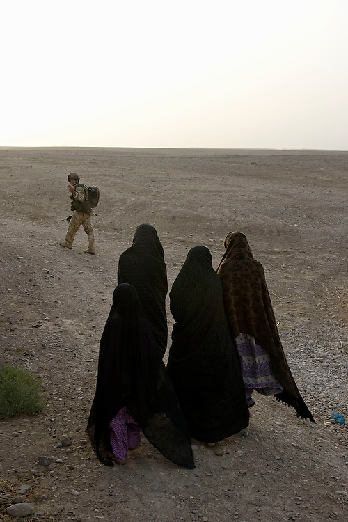 A British soldier of 3rd Battalion The Parachute Regiment leads a group of Afghan women to a safe location during a search for insurgents after a dawn assault on a compound as part of Operation 'Southern Beast'. Kandahar Province, Afghanistan on the 6th of August 2008.