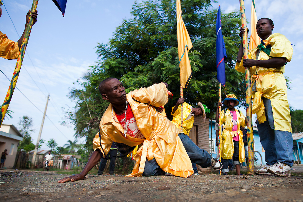 Dominican Republic: A lead Flag bearer performs a ritual at a crossroads as part of the GaGá  procession of El GaGá de San Luis....
