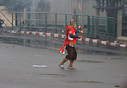 """A """"Red Shirt' supporter fires a sling shot at police and military forces on the streets of Bangkok...Violence between the 'Red Shirts' of the UDD and police / government military forces on the city streets of Bangkok. The UDD (United Front for Democracy Against Dictatorship) says Prime Minister Abhisit Vejjajiva came to power illegitimately and is a puppet of the military. The movement is made up of supporters of former Prime Minister Thaksin Shinawatra who was ousted in a coup in September 2006. The UDD wants Mr Abhisit to resign and call fresh elections."""