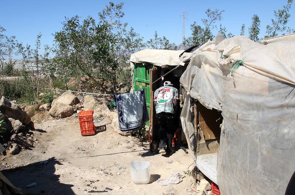 """EUROPE - SPAIN - EL EJIDO ; Illegal Immigration - VEGETABLE & FRUIT Production in Andalusia ; EL PLASTICO ; Exploitation of African workers;.The fruits and vegetables grown in the area are worth about $1.8 billion a year. Most of the workers are Moroccans, often called """"Moros"""" in reference to the Moors who ruled southern Spain for 700 years; Europa - SPANIEN - Landwirtschaft.Die Region um El Ejido, Provinz Almeria in Andalusien, gilt als Europas  größter agrarindustriell genutzter """"Wintergarten"""". Unter ca. 36.000 Hektar Plastik (Treibhäusern) wird ganzjährig Obst und Gemüse angebaut, welches zum Großteil in Supermärkten in Nordeuropa, Deutschland und England verkauft wird... Unter den Plastikplanen werden ca. 60.000, meist illegale Einwanderer aus Marokko, Schwarzafrika, Osteuropa beschäftigt. Arbeitsschutz und Mindestlöhne werden nicht eingehalten. .HIER: Mohamed, 25, aus dem Senegal, tagsüber vor seiner Hütte ohne Job. Die meisten der papierlosen Migranten leben in so genannten Chabolas, Hütten aus notdürftig zusammengezimmerten Paletten und Plastikplanen. Tagsüber arbeiten sie als Tagelöhner in den Gewächshäusern, abends kehren sie in ihre Behausungen zurück, wo es weder sanitäre Anlagen, noch fließendes Wasser oder Elektrizität gibt. Südlich von El Ejido....23.03.2007.Copyright: Christian Jungeblodt"""