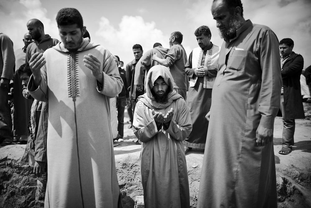 Des proches de Whalid Zidane (34 ans, chauffeur de taxi et combattant rebelle tué le 31 mars 2011 sur la ligne de front entre Aj Dabiya et Brega) prient devant son corps, lors de ses funérailles dans la ville de Koueffia, dans la banlieue de Benghasi.