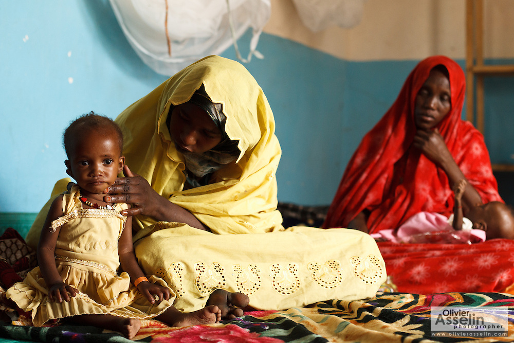A girl who suffers from acute malnutrition sits next to her mother at the UNICEF-sponsored Mao therapeutic feeding center in the town of Mao, Kanem region, Chad on Monday February 13, 2012.